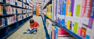 boy reading on floor between library shelves